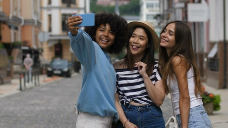 Friends taking selfies in the middle of a street