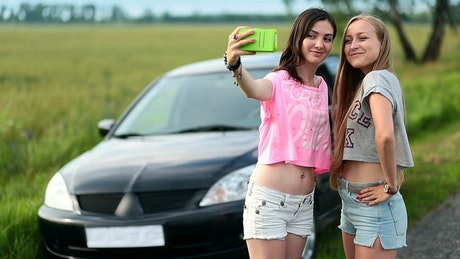Friends taking selfies with parked on a road