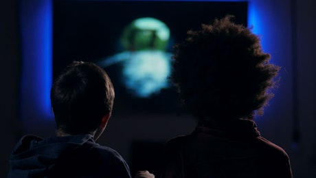 Friends watching a film in a dark room