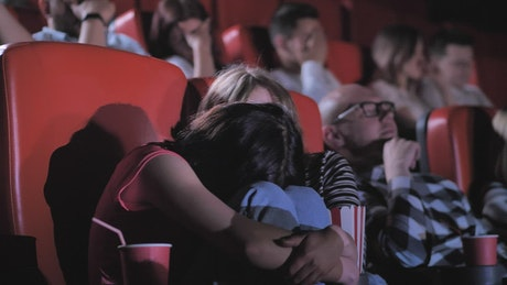Friends watching a horror film in the cinema