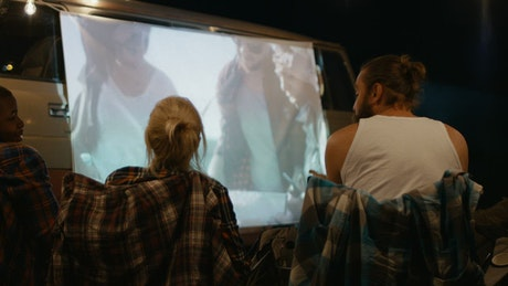 Friends watching a movie at the campsite