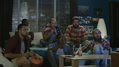 Friends watching a sports game at home