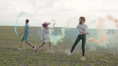 Friends with colored smoke bombs