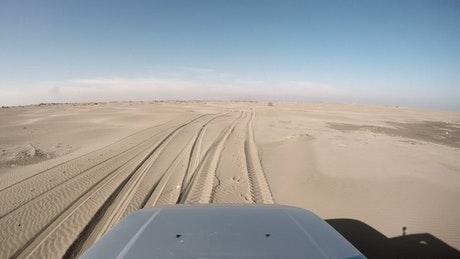Front view of a car driving through the desert