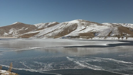 Frozen water surface of a lake near the mountains