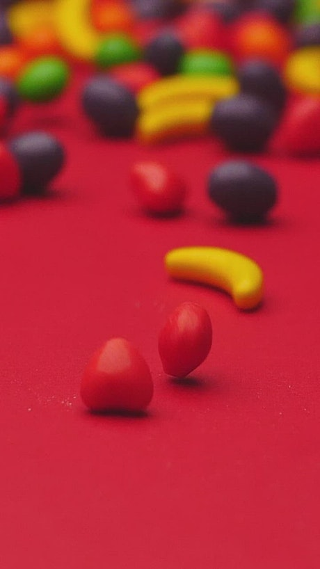 Fruit shaped sweets rolling on a red surface