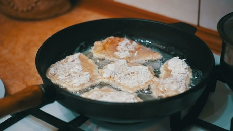 Frying meat in a frying pan with oil