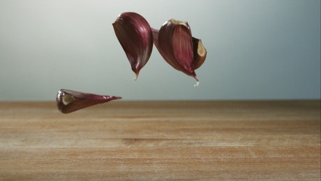 Garlic pieces falling to the table in slow motion