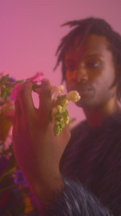 Gay man appreciating flowers in a feminine environment