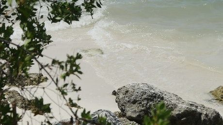 Gentle waves on the beach and a rock