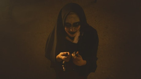 Ghostly nun kneeling in the church