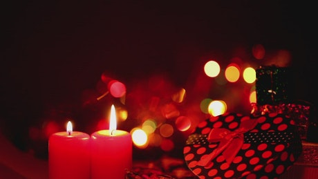 Gifts and candles with flashing lights in the back