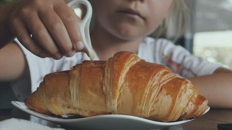Girl adding sweet milk on a croissant