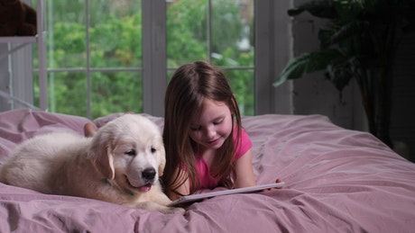 Girl and her puppy watching videos