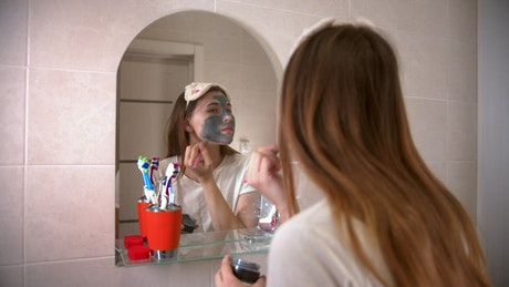 Girl applying a mask in front of a mirror