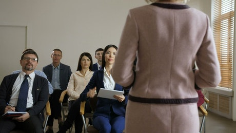 Girl asking in a formal meeting with more people