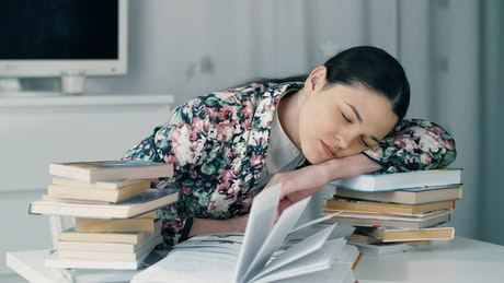 Girl bows her head exhausted from studying