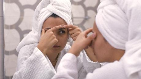 Girl carefully examining her face in her bathroom mirror