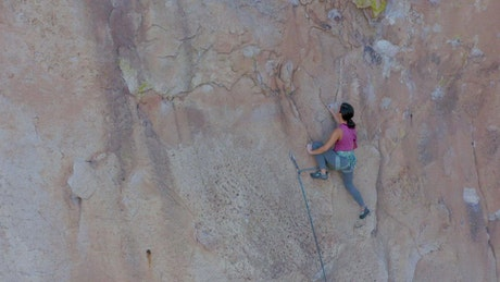 Girl climbing a very steep mountain