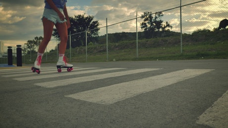 Girl crossing an empty street skating on roller skates