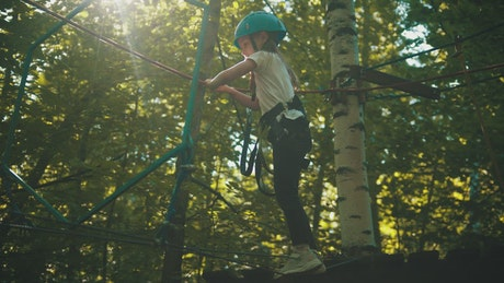 Girl crossing the ropes in the woods