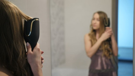 Girl curling her hair in front of a mirror