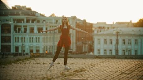 Girl dancing ballet on top of a building