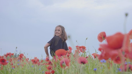 Girl dancing happily in a field of flowers