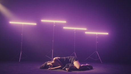 Girl dancing on the floor illuminated by neon lights