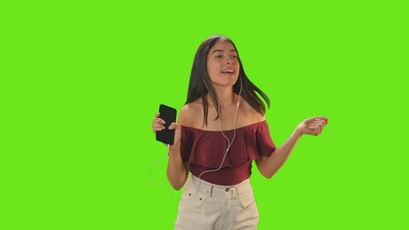 Girl dancing with her earphones on a green background
