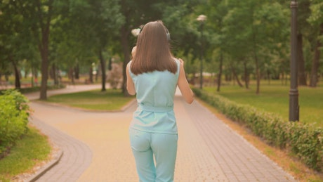 Girl dancing with her headphones while taking a walk