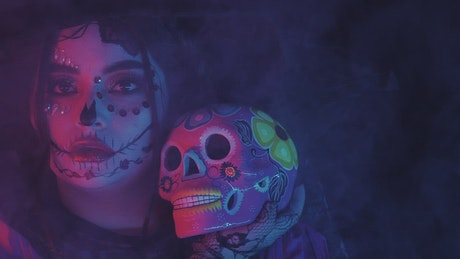 Girl disguised as a catrina in the dark