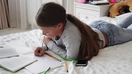 Girl doing her homework on her bed