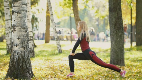 Girl doing stretching in a sunny park