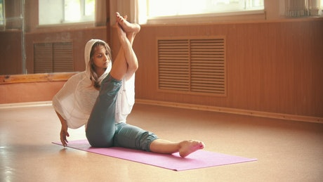 Girl doing stretching on a mat on the floor