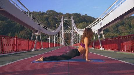 Girl doing yoga on a pedestrian bridge