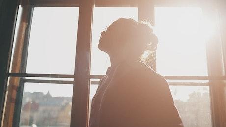 Girl enjoying music dances by sunlit window