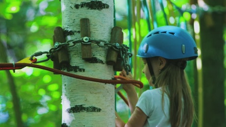 Girl fastened to a harness crosses a forest