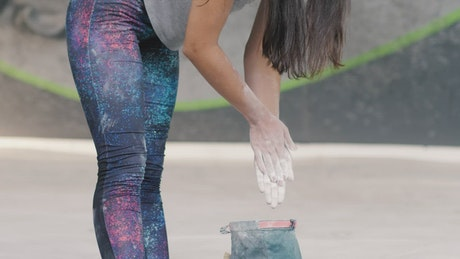 Girl filling her hands with chalk before practicing mountaineering