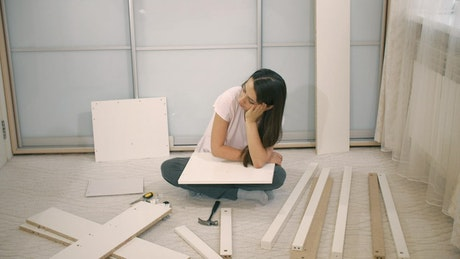 Girl frustrated when assembling a furniture