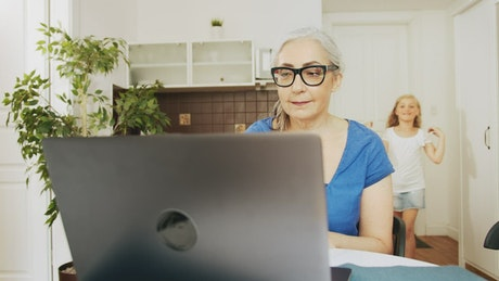 Girl greets grandma while she works on laptop
