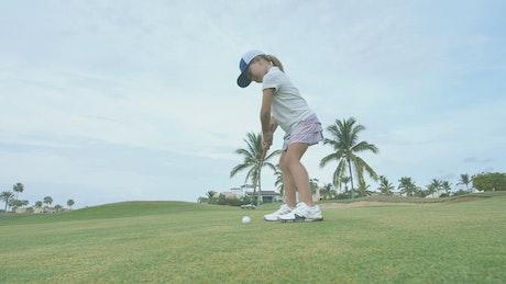 Girl hitting a golf ball