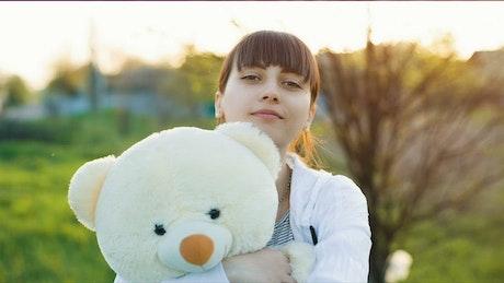 Girl hugging a teddy bear outdoors