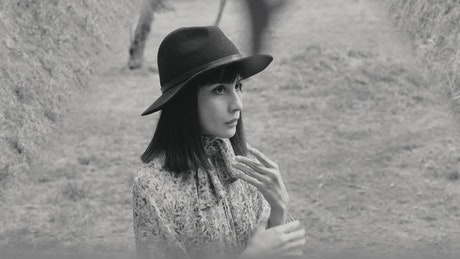Girl in a forest arranging her hat in black and white