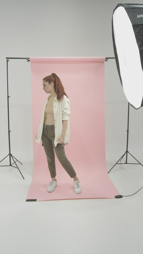 Girl in a photographic set modeling on a pink background