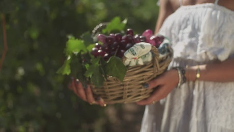 Girl in a white dress holding grapes