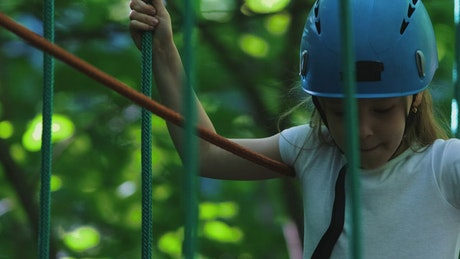 Girl in an a rope adventure in a park