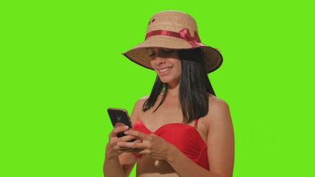 Girl in beachwear takes a selfie on green screen