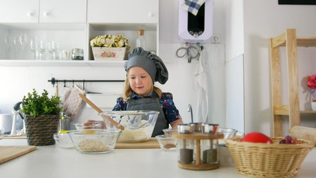 Girl in the kitchen preparing a mixture in a bowl
