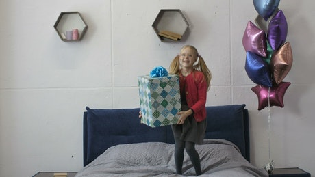 Girl jumping with a gift